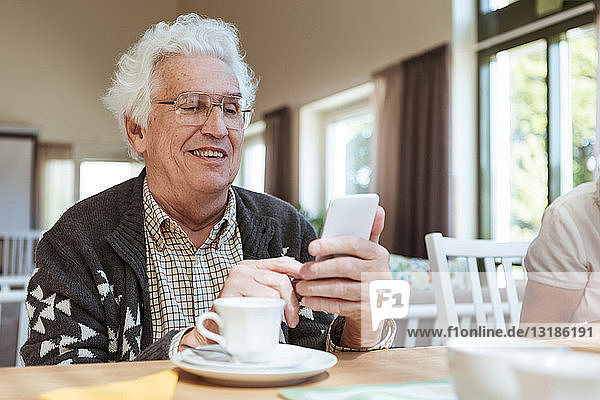 Senior man using mobile phone at breakfast table in nursing home