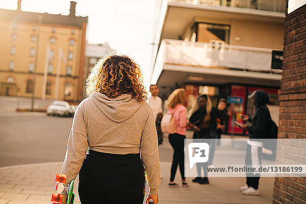 Rückansicht einer Frau mit Skateboard  die auf Freunde in der Stadt zugeht