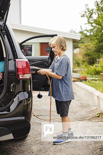 Seitenansicht in voller Länge eines Mädchens  das ein Elektroauto auf der Einfahrt auflädt