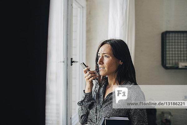 Kreative Geschäftsfrau spricht am Smartphone  während sie im Büro am Fenster steht