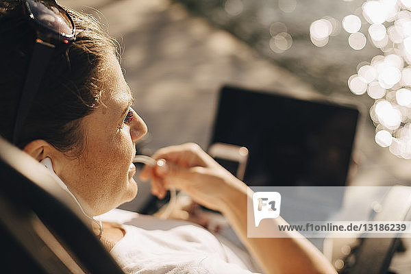High angle close-up of woman talking through headphones during summer