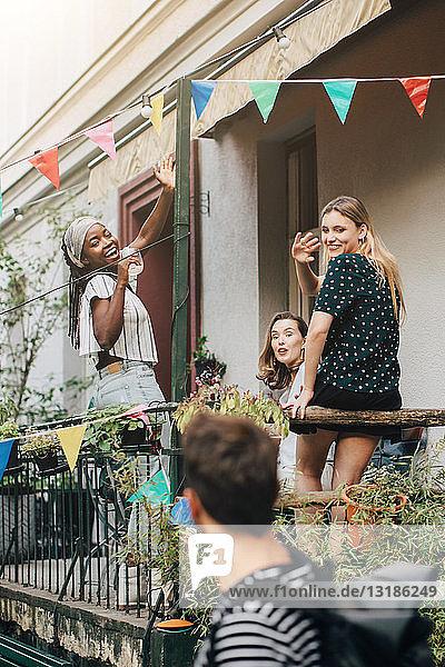 Glückliche junge Frauen winken einem männlichen Freund zu  während sie während einer Party auf dem Balkon stehen