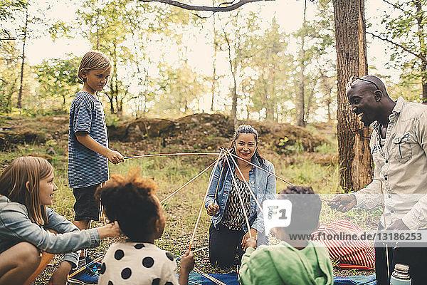 Multi-ethnische Familie spielt mit Spießen am Picknickplatz im Park