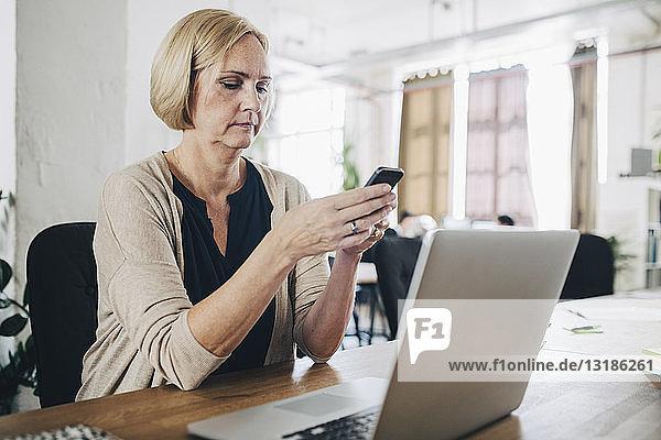 Reife Geschäftsfrau benutzt Mobiltelefon am Schreibtisch im Kreativbüro