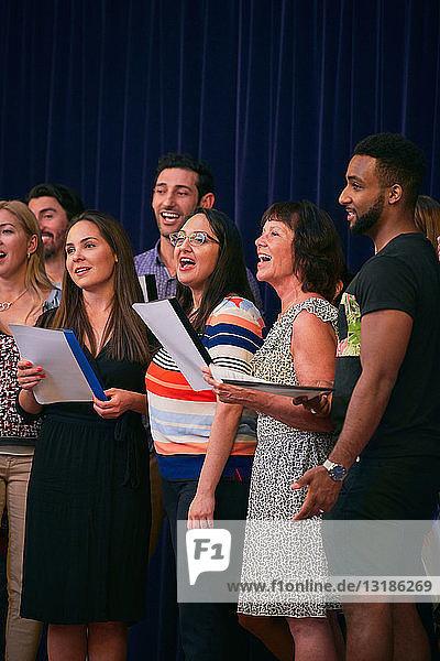 Multi-ethnische Menschen singen im Chor auf der Schulbühne