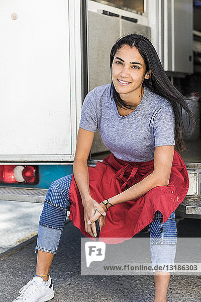 Portrait of confident young female owner sitting at food truck entrance