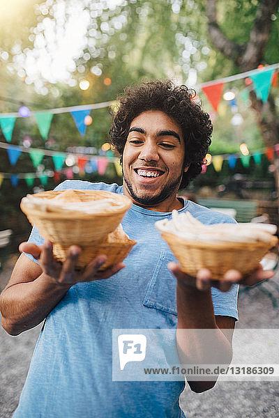 Lächelnder junger Mann trägt während Gartenparty Essen in Schüsseln