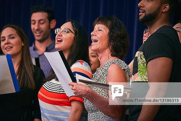 Multi-ethnische Chorsänger auf der Bühne im Auditorium