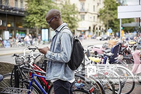 Seitenansicht eines mittelgroßen erwachsenen Geschäftsmannes  der ein Smartphone benutzt  während er in der Stadt an den Fahrrädern steht