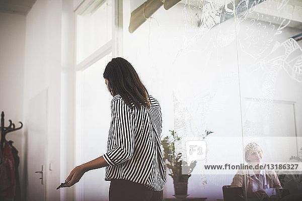 Kreative Geschäftsfrau gestikuliert  während sie im Sitzungssaal im Büro steht