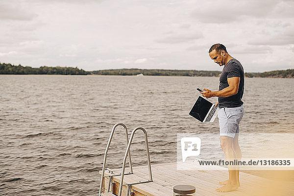 Mann in voller Länge mit Laptop  der das Telefon benutzt  während er auf dem Steg gegen den Himmel steht