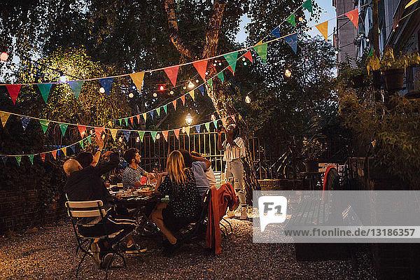 Junge Frau fotografiert Freunde während einer Dinnerparty im Hinterhof