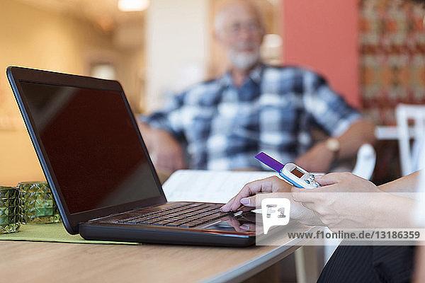 Ausgeschnittenes Bild einer Altenpflegerin  die im Pflegeheim Medikamente online mit Laptop und Kreditkarte kauft