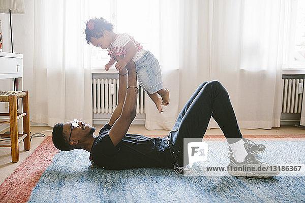 Verspielter Vater hebt Tochter hoch  während er zu Hause auf dem Teppich liegt