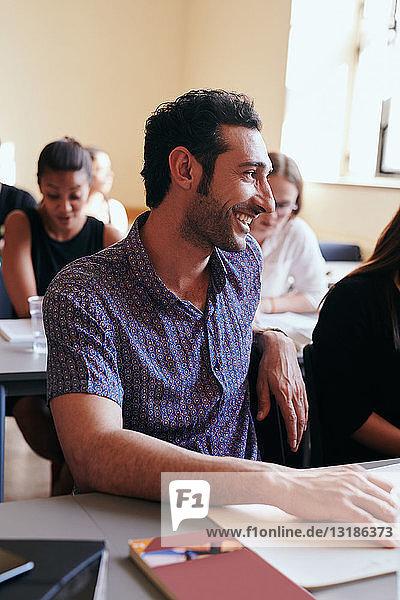 Junger Mann lächelt beim Wegschauen in der Sprachschule