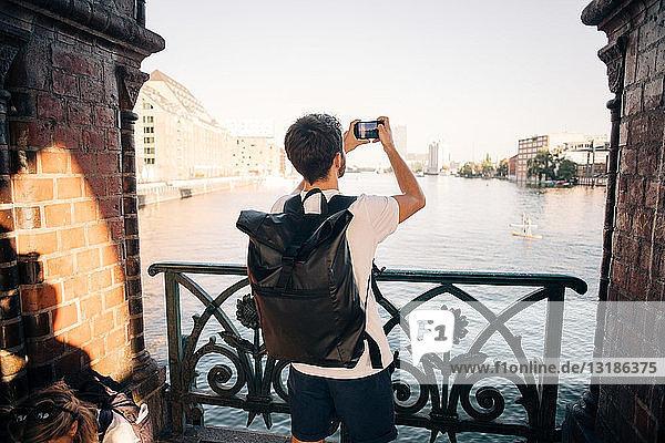 Rückansicht eines jungen Mannes  der mit einem Smartphone in der Stadt einen Fluss fotografiert