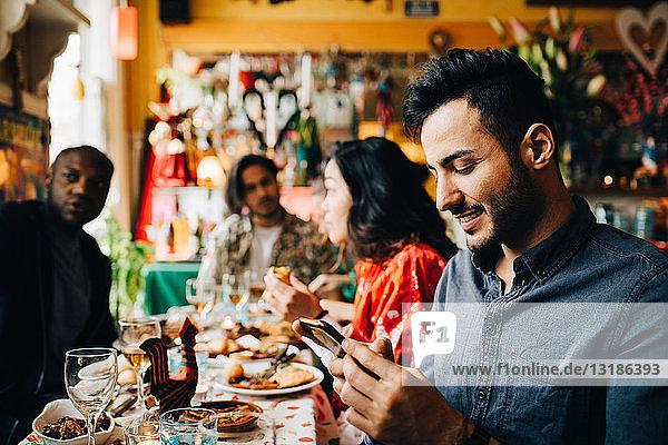 Lächelnder junger Mann sendet Textnachrichten auf einem Smartphone,  während er während der Dinnerparty mit Freunden im Restaurant am Tisch sitzt