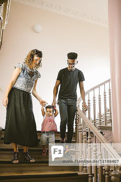 Familie in voller Länge auf der Wohnungstreppe nach unten