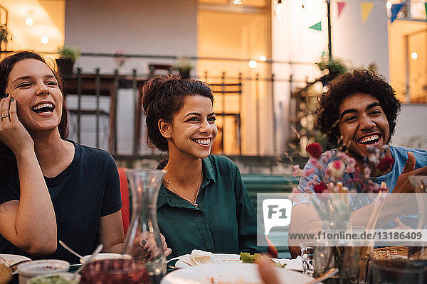 Happy young friends enjoying dinner party in backyard