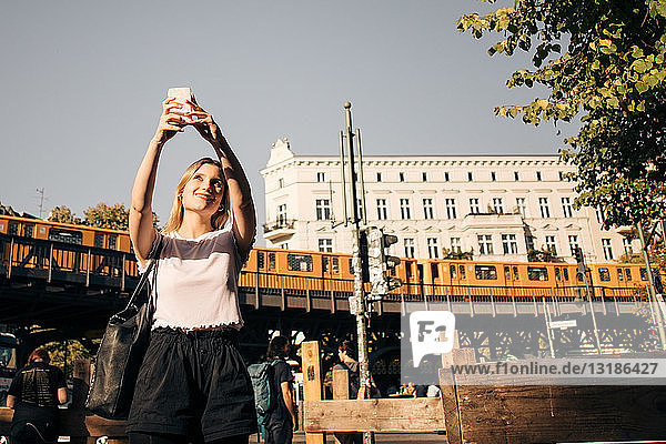 Junge Frau  die auf der Straße in der Stadt auf der Straße steht und sich per Handy selbstständig macht