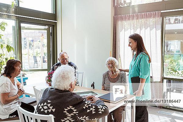 Weibliche Gesundheitshelferin im Gespräch mit älteren Menschen im Pflegeheim