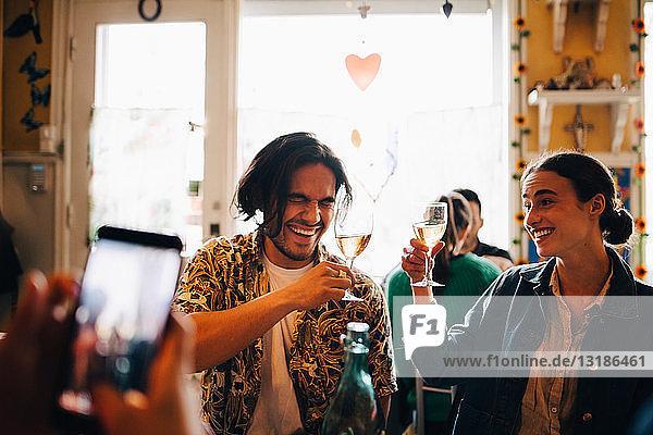 Mann fotografiert fröhliche junge Freunde  die während des Brunch im Restaurant einen feierlichen Toast ausbringen
