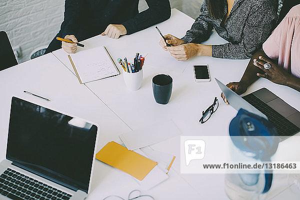 Ein Teil der kreativen Geschäftsleute sitzt am Konferenztisch im Sitzungssaal