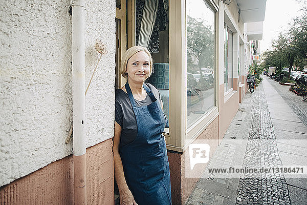 Porträt einer selbstbewussten Besitzerin  die am Eingang der Polsterei steht