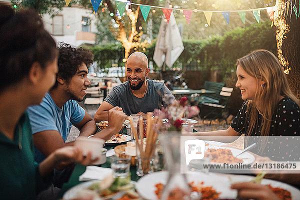 Lächelnder junger Mann und lächelnde Frauen lauschen dem Gespräch eines männlichen Freundes während einer Dinnerparty im Hinterhof