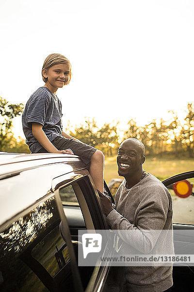 Porträt eines lächelnden Mannes von Tochter auf dem Autodach bei Sonnenuntergang im Park sitzend