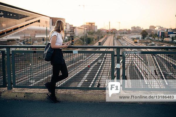 Seitenansicht einer jungen Frau  die bei Sonnenuntergang auf einer Brücke über Eisenbahnschienen in der Stadt steht
