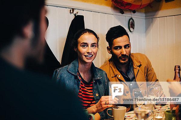 Junger Mann und Frau betrachten einen männlichen Freund während einer Dinnerparty im Restaurant