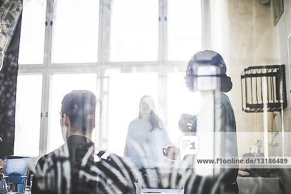 Kreative Geschäftsleute bei Diskussionen im Sitzungssaal durch gemustertes Glas gesehen