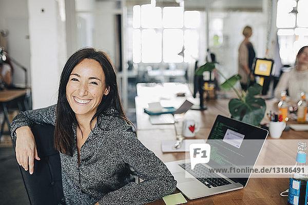 Porträt einer lächelnden Computerprogrammiererin  die am Schreibtisch im Kreativbüro sitzt