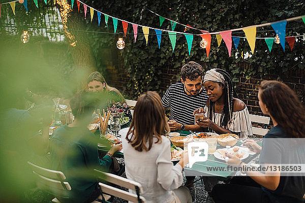 Junge männliche und weibliche Freunde mit Essen am Tisch während einer Dinnerparty im Hinterhof