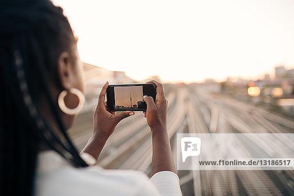 Junge Frau fotografiert Fernsehturm bei Sonnenuntergang per Handy