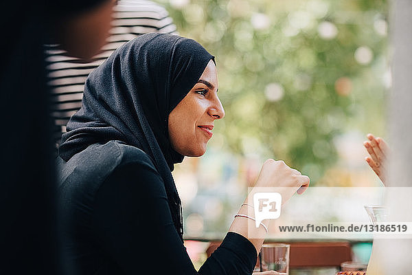 Young woman in hijab looking away while sitting at balcony during party