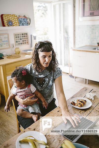 Mutter benutzt Laptop  während sie mit der Tochter zu Hause am Tisch sitzt