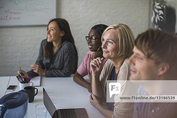 Lächelnde kreative Geschäftsleute hören zu  während sie im Konferenzraum sitzen
