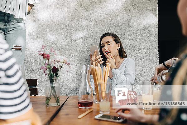 Junge Frau schaut auf Handy  während sie mit Freunden während einer Party auf dem Balkon sitzt