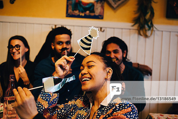 Fröhliche junge Frau hält Requisiten  während sie während der Dinnerparty im Restaurant gegen multi-ethnische Freunde sitzt