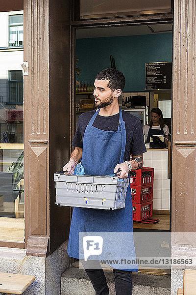 Junger männlicher Besitzer trägt Kiste gegen Restaurant