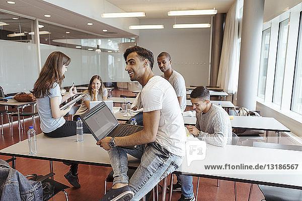 Lächelnder Mann benutzt Laptop  während er mit Freunden im Klassenzimmer der Universität sitzt