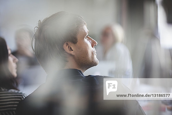 Rückansicht eines Geschäftsmannes  der während einer Sitzung im Sitzungssaal sitzt