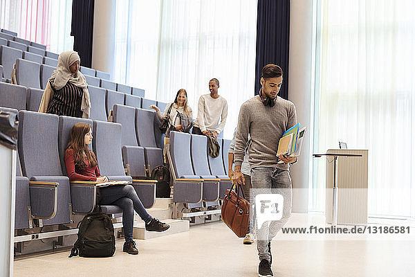 Mann geht mit Büchern gegen Freunde im Hörsaal