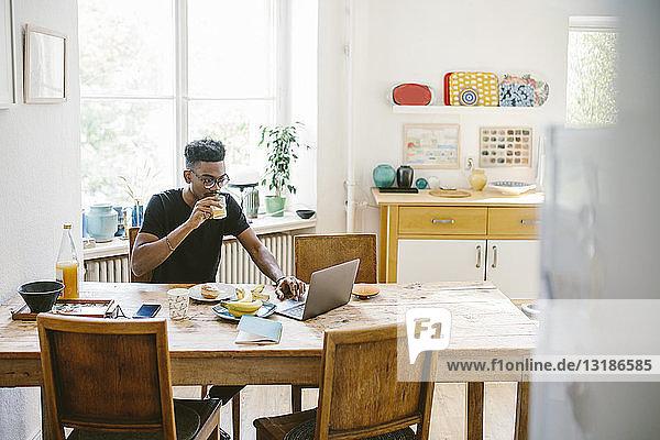 Junger Mann trinkt Saft  während er seinen Laptop am Tisch im Haus benutzt