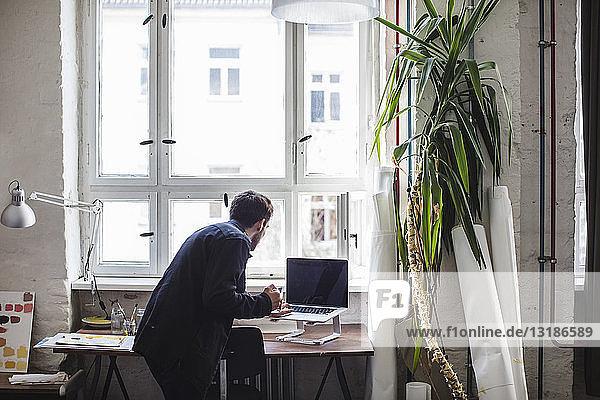 Geschäftsmann mit Laptop am Schreibtisch im Kreativbüro