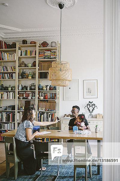 Eine Frau zeigt einem jungen Mann  der mit seiner Tochter zu Hause am Tisch sitzt  ein Handy