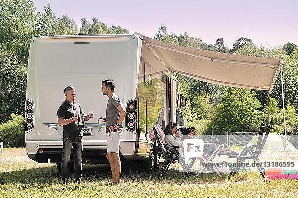 Älterer Mann unterhält sich mit seinem Sohn  während sich die Familie vor dem Lieferwagen auf dem Campingplatz entspannt