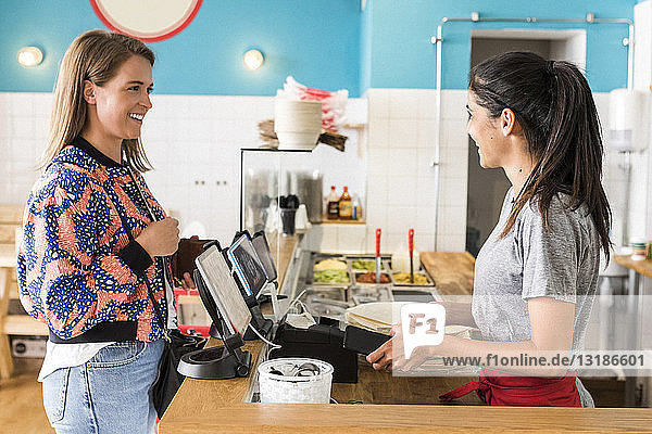 Side view of smiling female customer and owner talking while standing at checkout in restaurant